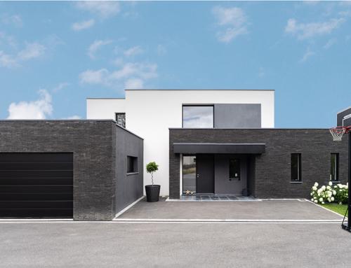 Construction d'une maison cubique, enduit et briques noires